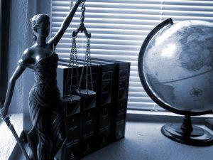 Estatuilla de la Justicia con libros y mapamundi